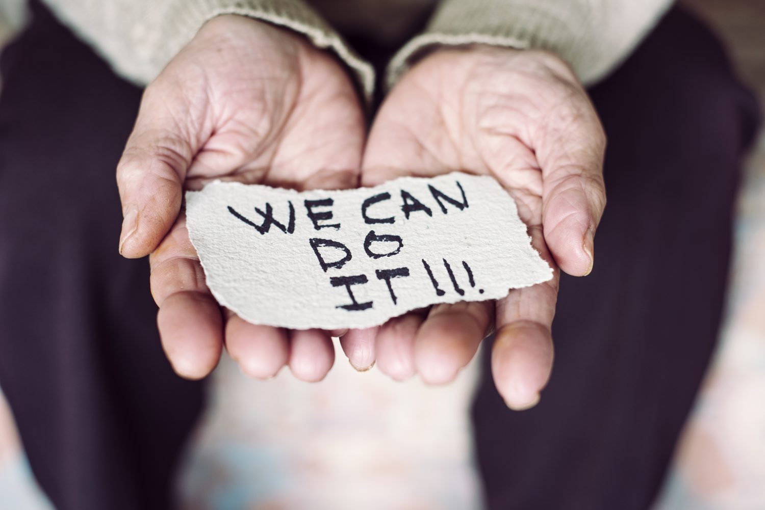 closeup of an old caucasian woman indoors with a piece of paper in her hands with the text we can do it written in it